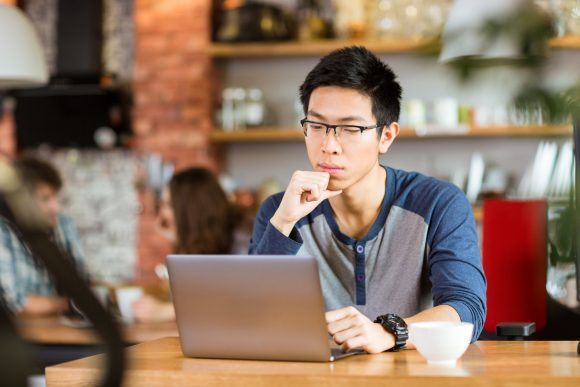 Concentrated asian man sitting in cafe, thinking and using laptop